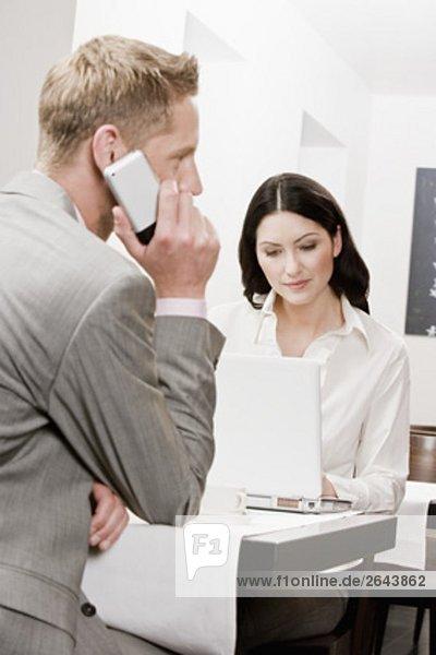 Bunsinessman und Frau Kollegin im Restaurant am Handy sprechen und arbeiten mit Laptop-computer