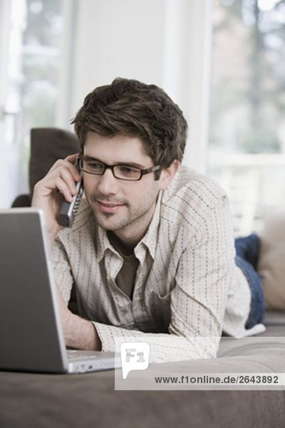 Interior  zu Hause  Portrait  Mann  Computer  Notebook  sprechen  arbeiten  Telefon  jung