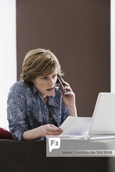 Interior  zu Hause  Frau  Computer  Notebook  sprechen  Telefon  jung