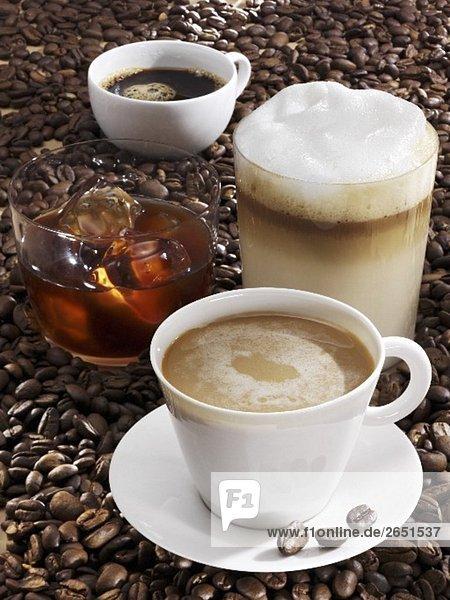 Vier verschiedene Kaffeegetränke auf Kaffeebohnen - Foodcollection ...