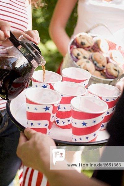 Frau giesst Kaffee in Pappbecher (4th of July  USA)