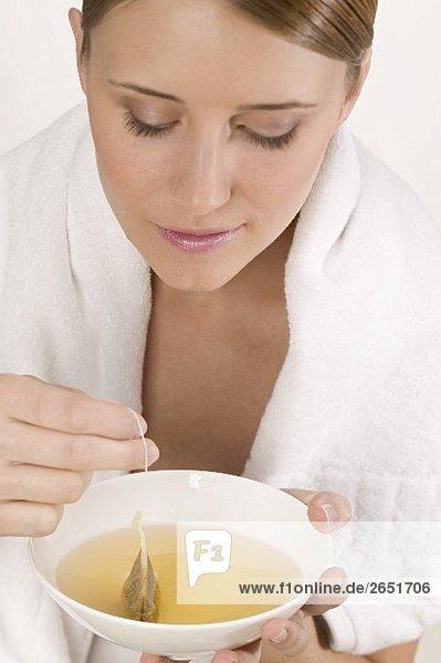 Frau mit weissem Handtuch und Schale Tee