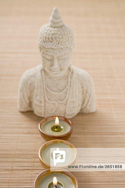 Drei Windlichter vor Buddhastatue auf Bambusmatte