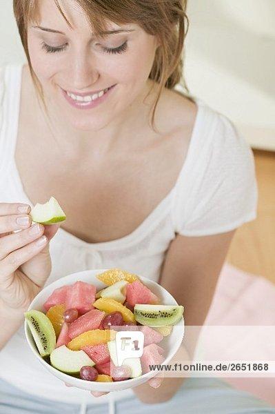 Frau isst Apfelschnitz von Obstsalat