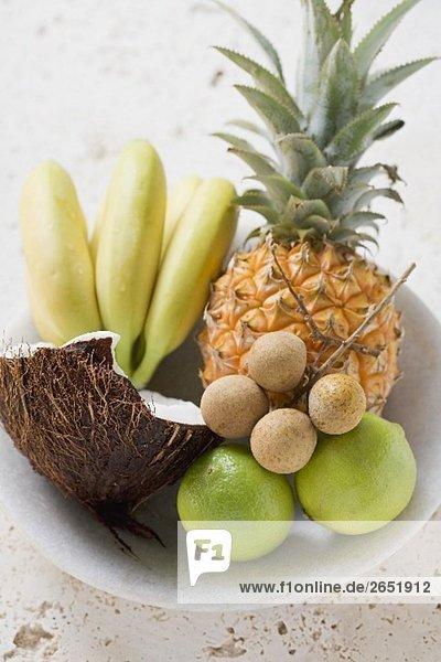 Obstschale mit exotischen Früchten  Limetten und Kokosnuss
