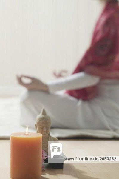 Woman sitting cross-legged  candle and Buddha statue