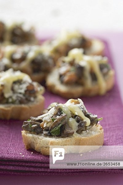 Überbackene Baguettescheiben mit Pilzen und Käse