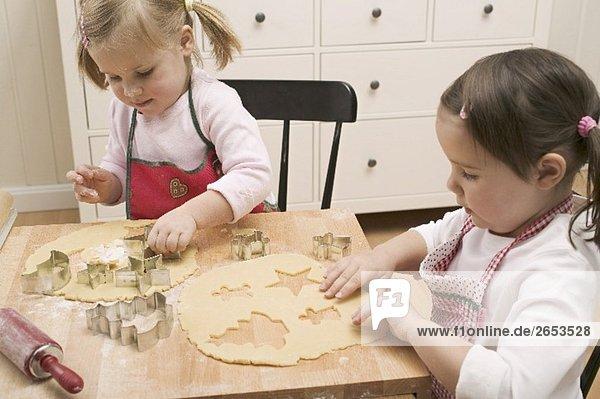 Zwei kleine Mädchen stechen Plätzchen aus