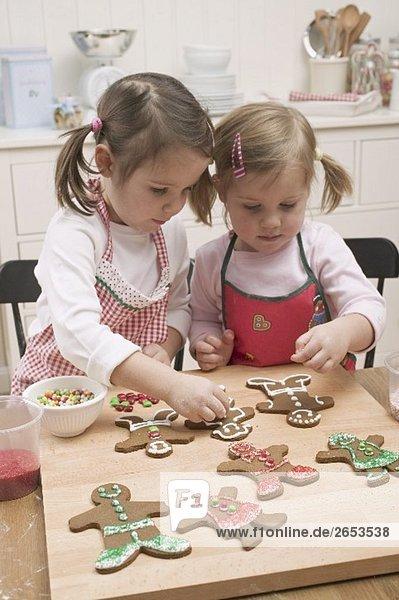 Zwei kleine Mädchen verzieren Lebkuchenfiguren