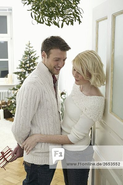 Couple under mistletoe  man holding Christmas gift