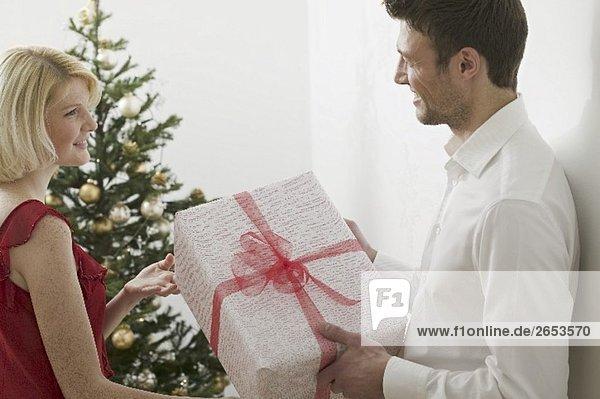 Paar mit Weihnachtsgeschenk vor Christbaum