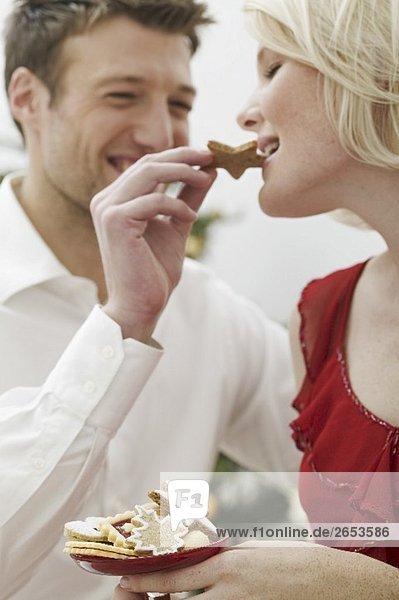 Mann füttert Frau mit Weihnachtsplätzchen