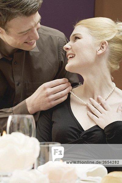 Mann legt Frau Perlenkette um den Hals