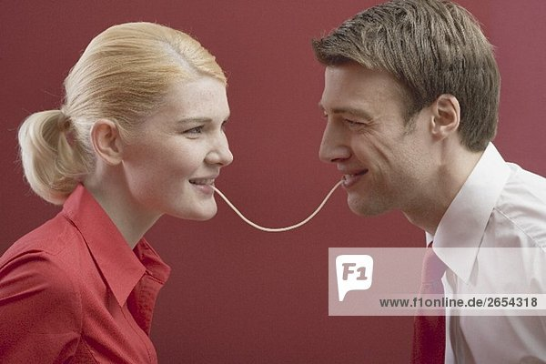 Couple eating a strand of spaghetti from both ends