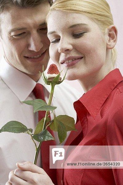 Romantisches Paar mit Schokoladenerdbeere auf Rosenstiel