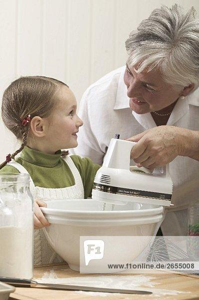 Grossmutter zeigt Enkeltochter das Rühren von Teig