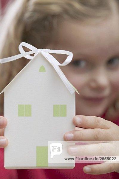 Kleines Mädchen hält Papierhaus (Weihnachtsgeschenk)