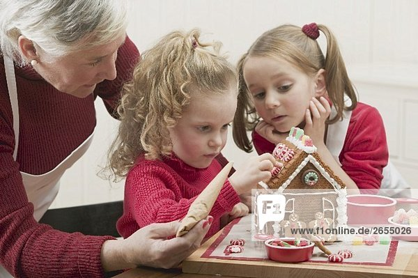 Small girls and grandmother decorating gingerbread house