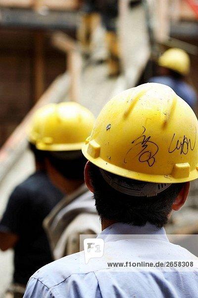 Bauarbeiter mit gelben Schutzhelme hinter
