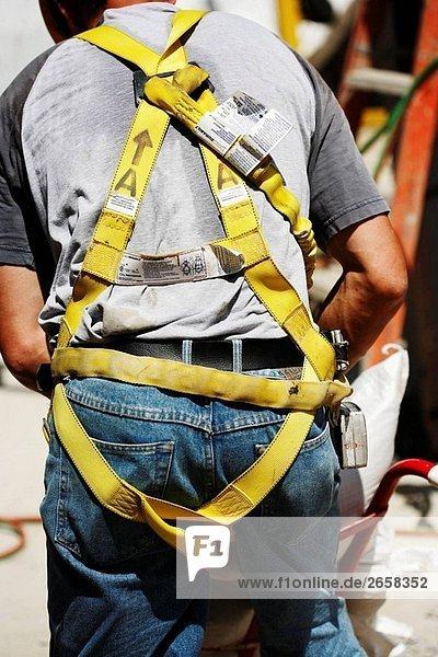Bauarbeiter von Rückseite tragen Sicherheitsgurt