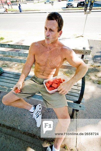 mit nacktem Oberkörper Man essen Stücke der Wassermelone aus einem Kunststoff-Container.