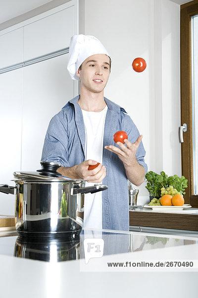 Mann jonglieren mit Tomaten in Küche