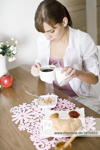 Frau pouring Milk in Kaffee