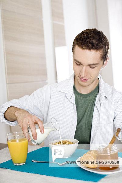 Mann pouring Milk in cornflakes