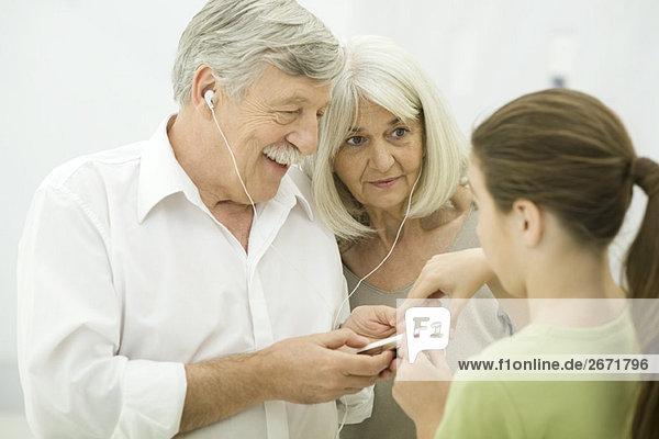 Junges Mädchen zeigt Großeltern den Umgang mit dem MP3-Player