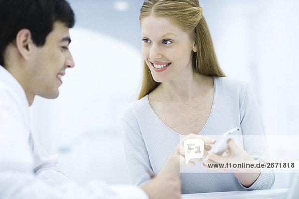 Professionelle Frau zeigt Handy an männlichen Kollegen