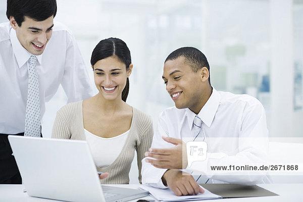 Junge Profis  die gemeinsam auf den Laptop schauen  lächelnd