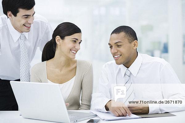 Junge Profis sitzen um Laptop-Computer  lächelnd