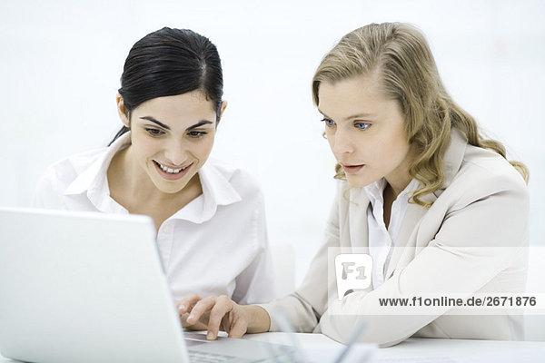 Professionelle Frauen  die zusammen auf den Laptop schauen  lächelnd