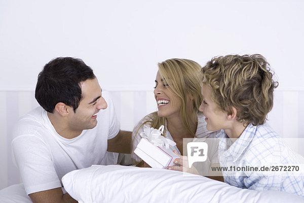 Familie zusammen im Bett liegend  Frau mit Geschenk