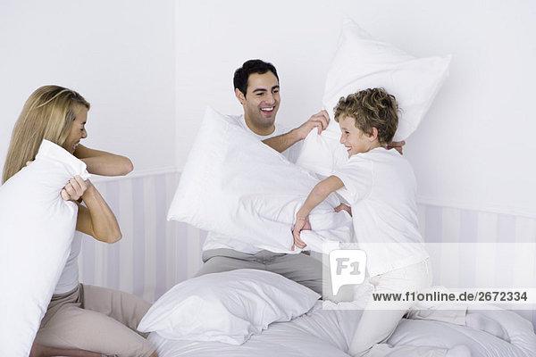 Familie mit Kissenschlacht auf dem Bett