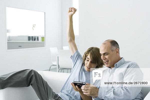 Jugendlicher Junge zeigt dem Vater ein tragbares Videospiel  Arm hochgezogen
