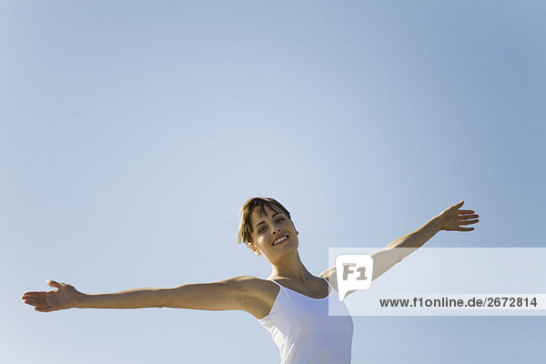 Woman standing outdoors with arms out  smiling at camera