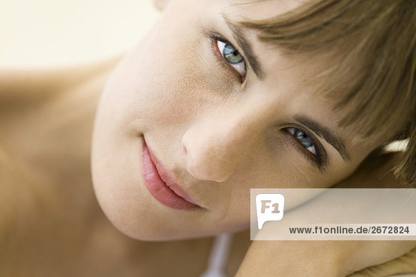 Woman smiling at camera  head resting on arm  portrait