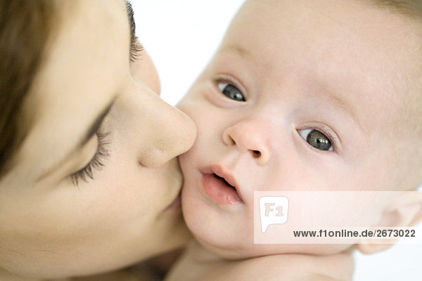 Mother kissing infant on the cheek  baby looking at camera