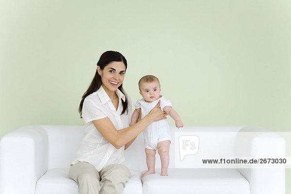 Frau hilft Baby auf der Couch stehen  lächelnd vor der Kamera