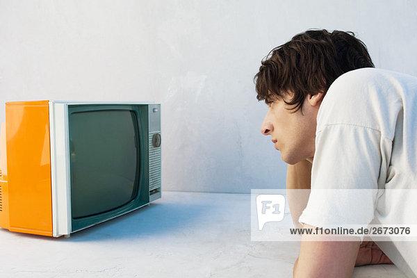 Junger Mann  der sich auf den Ellbogen lehnt und fernsieht.