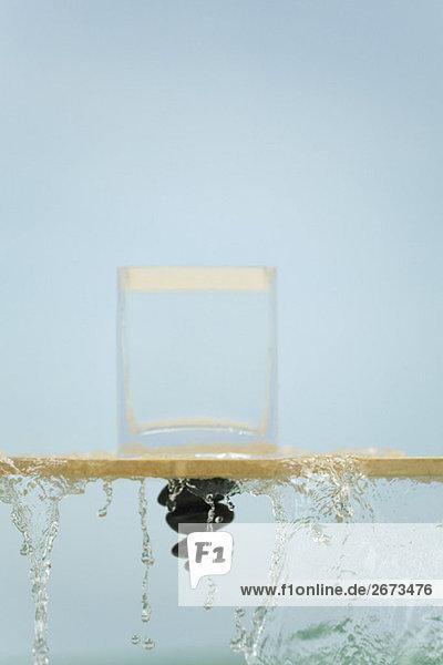 verkehrt herum Wasser Glas über fließen Fenstersims