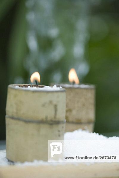 Kerzen in Bambus Halterungen umgeben von Schnee