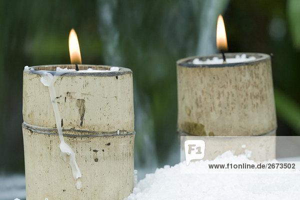 Brennende Kerzen in Bambus Halterungen umgeben von Schnee