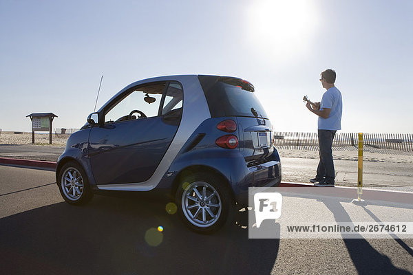 Young man standing by Smartcar at beach