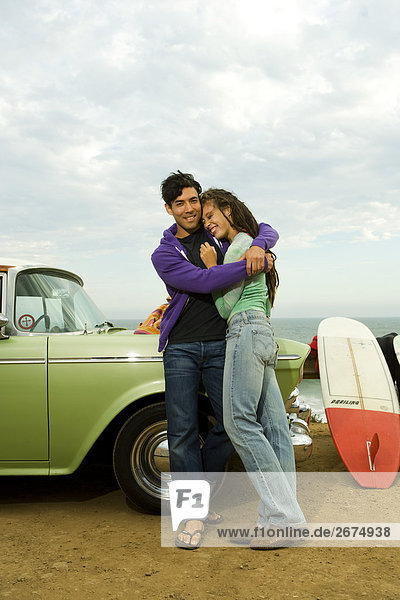 couple embrace on hood of vintage car at beach