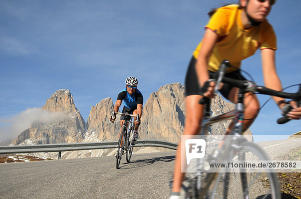 Two mountain bikers cycling together  Dolomites  Italy