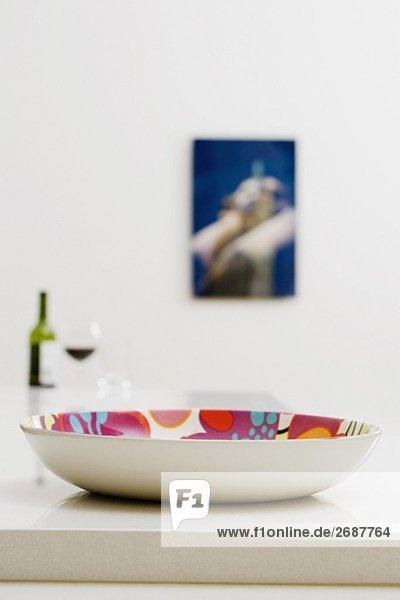 Nahaufnahme einer Schale auf einem Esstisch mit einer Flasche Rotwein im Hintergrund