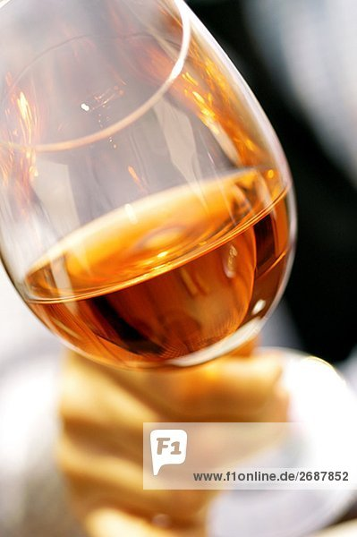 Close-up of a person's hand holding a glass of wine