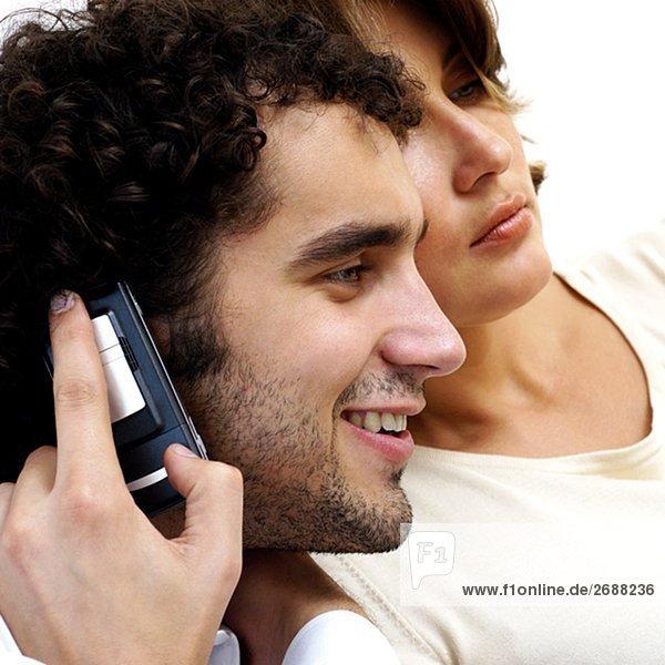 Junger Mann sprechen auf einem Mobiltelefon mit einer jungen Frau neben ihm
